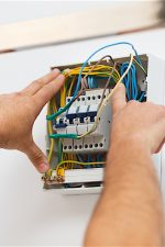 Electrician man installing electric fuse at home.
